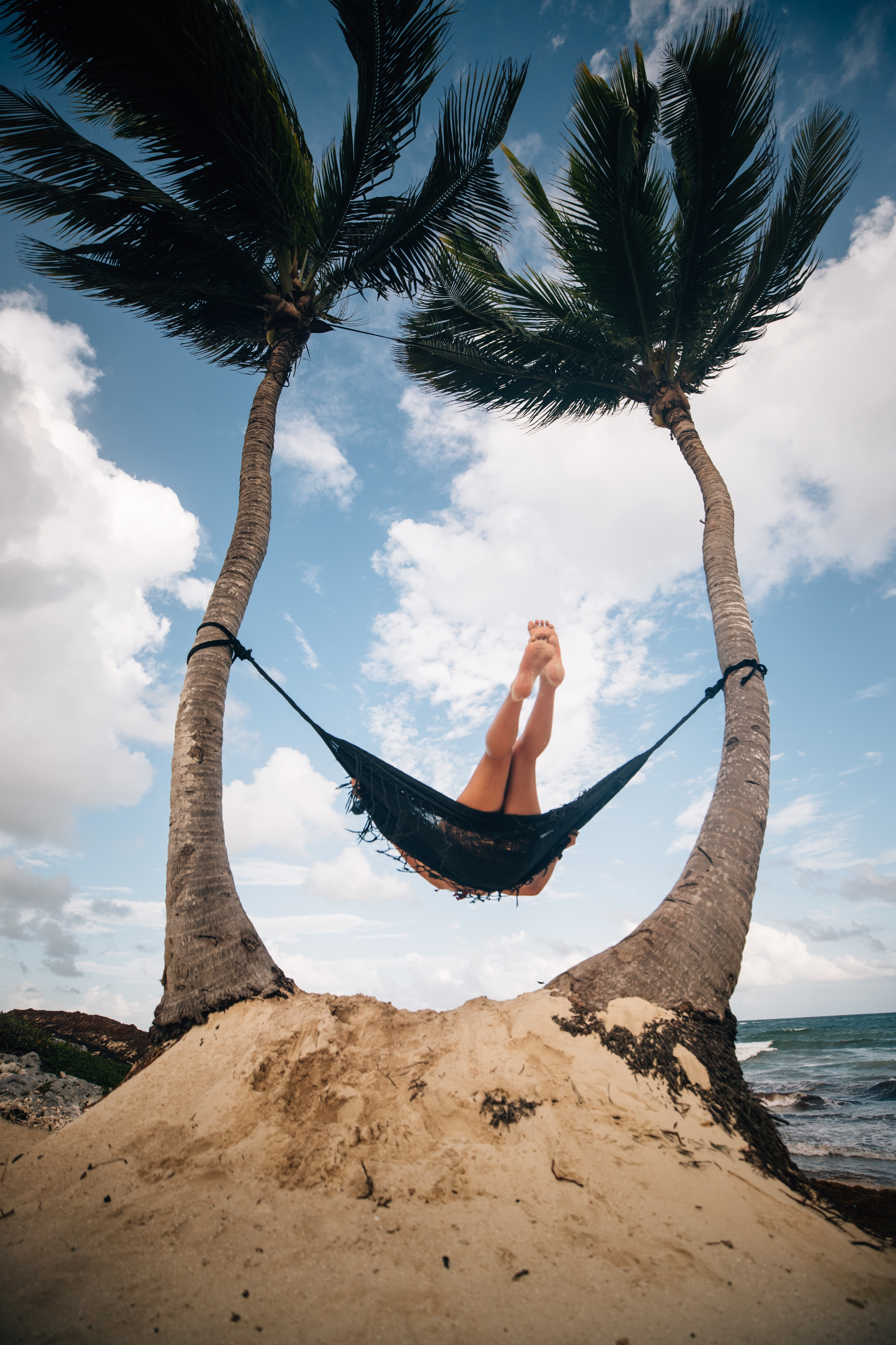 person riding on hammock near body of water