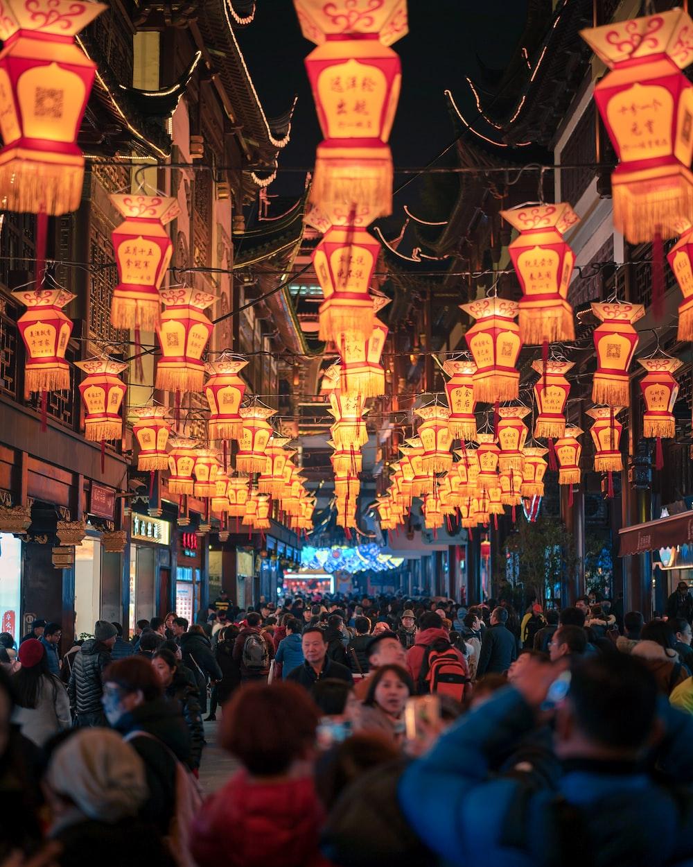people walking between establishments with lanterns above
