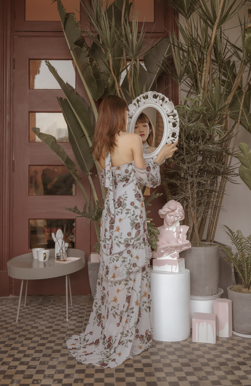 standing woman holding mirror
