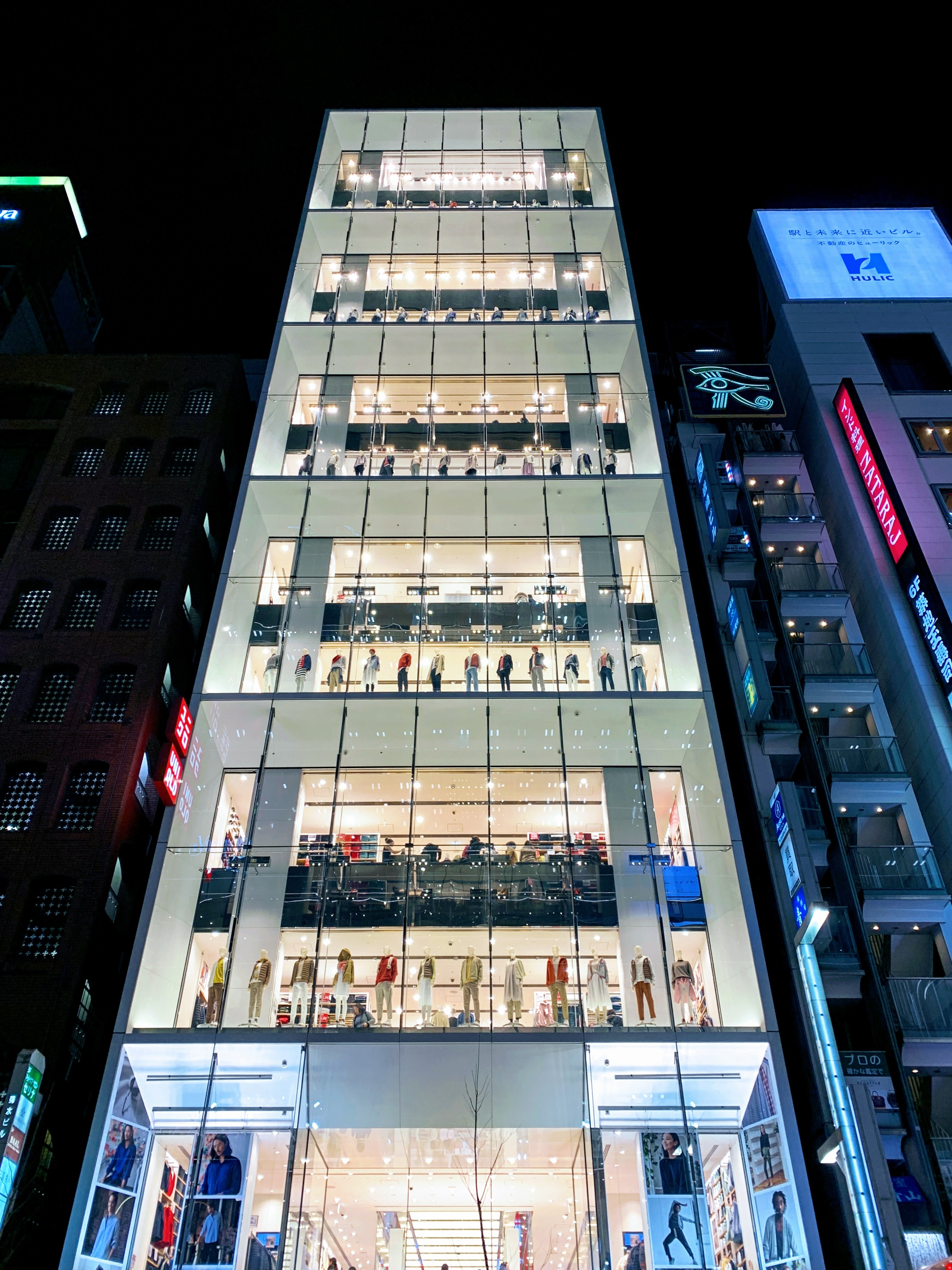 Tall retail building at night.