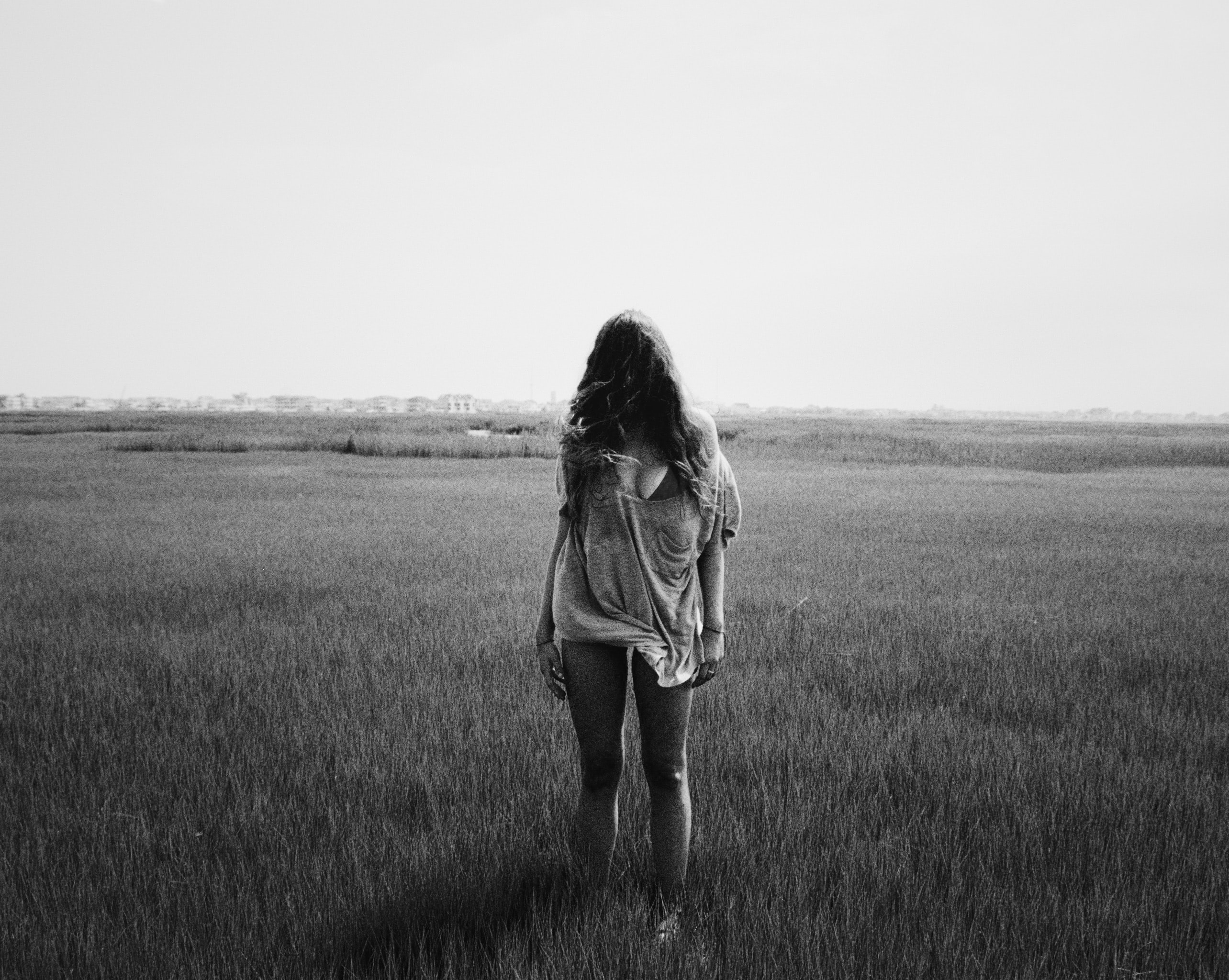 grayscale photography of standing woman on field during daytime