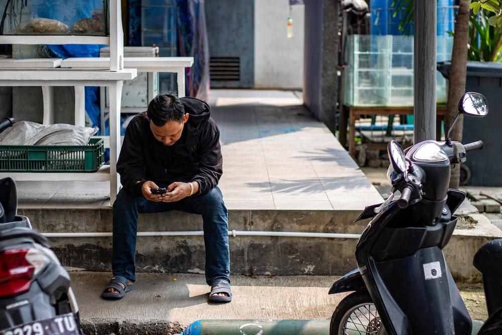 man sitting on pavement near motorcycles