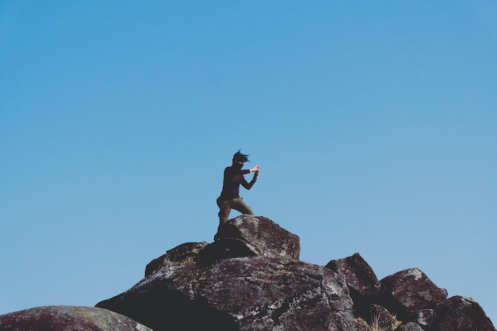 man standing on rocky mountain under blue sky