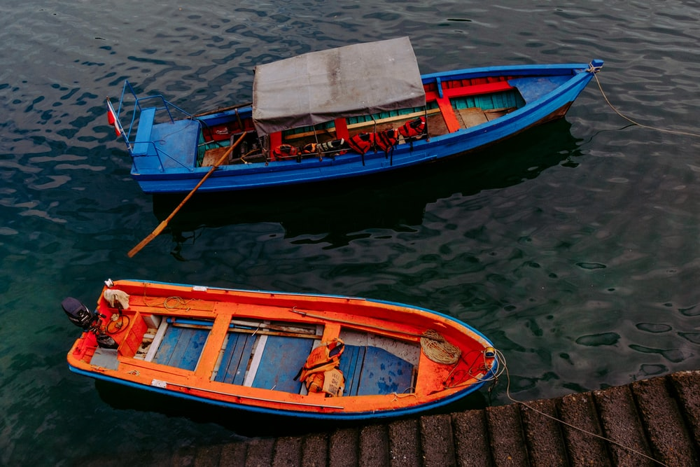 two blue and orange boat on dock