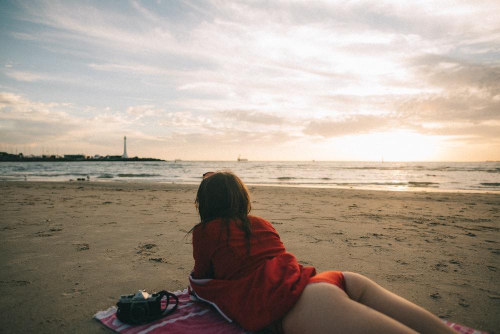 woman lying in prone position near shore