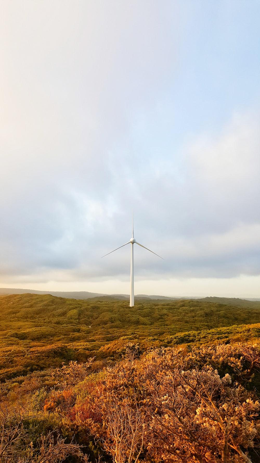 white wind turbine during daytime