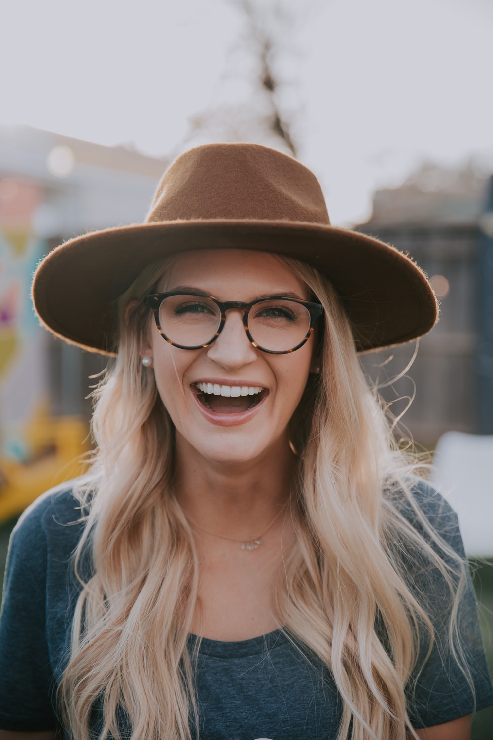 selective focus photography of smiling woman wearing brown hat