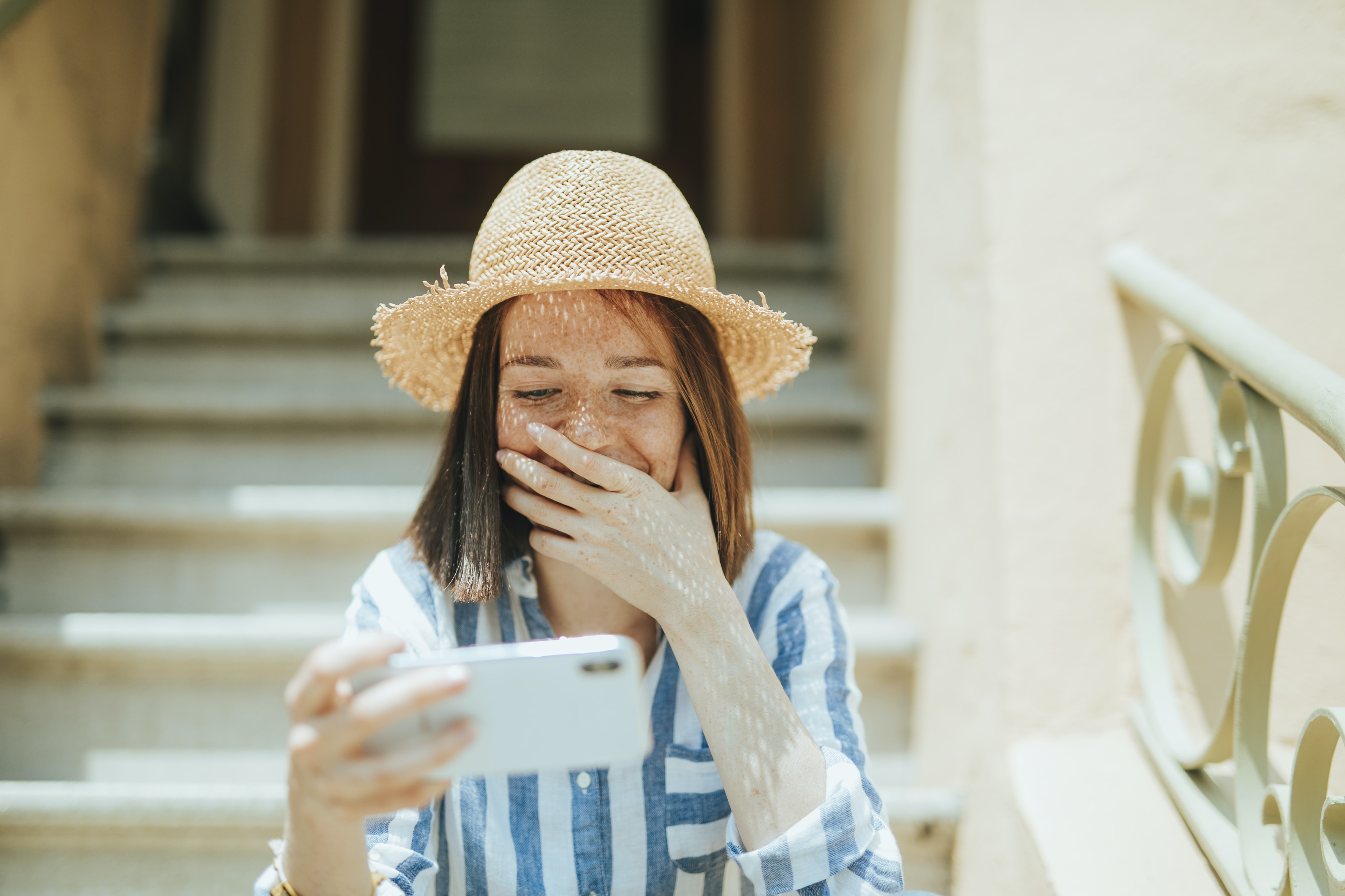 woman smiling while holding iPhone on stairs