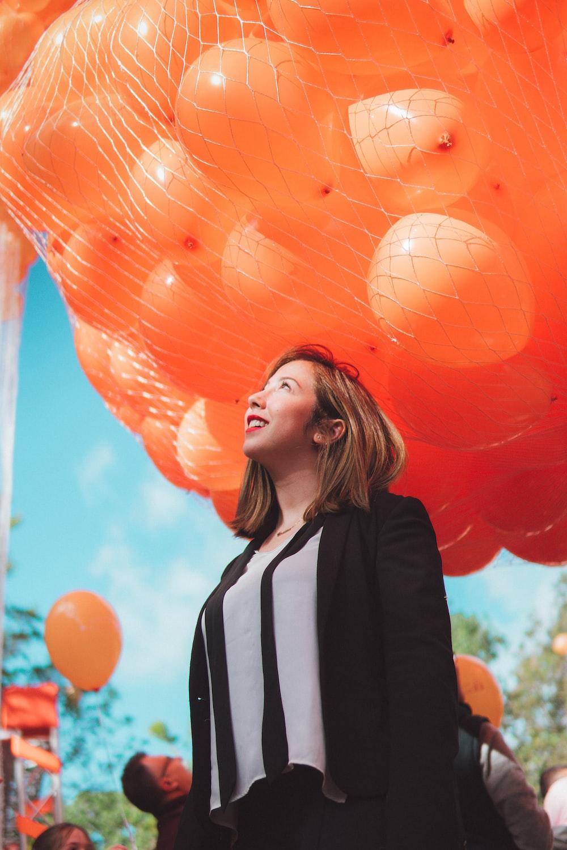 smiling woman under orange balloons during daytime
