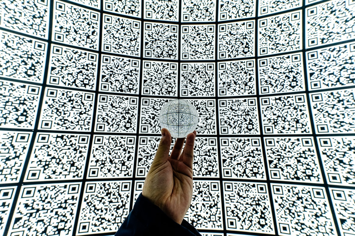 person holding clear glass ball with QR code background
