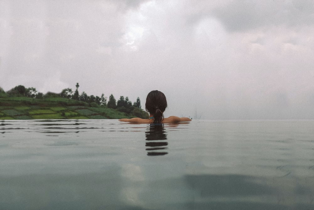 woman swimming on calm body of water