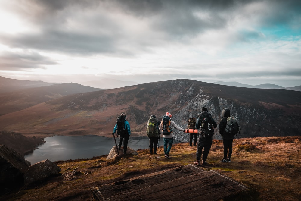 group of people on top of mountain under gray sky