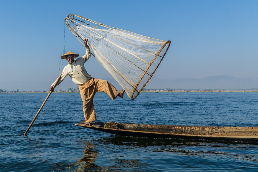 man holding stick and cone-shaped fishing net