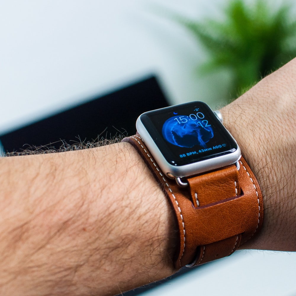 person wearing silver aluminum case Apple Watch with brown leather band