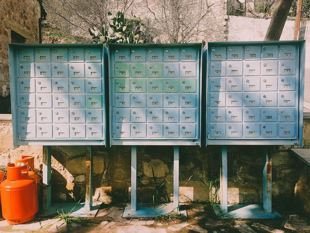 two orange propane tanks place beside three metal mailboxes