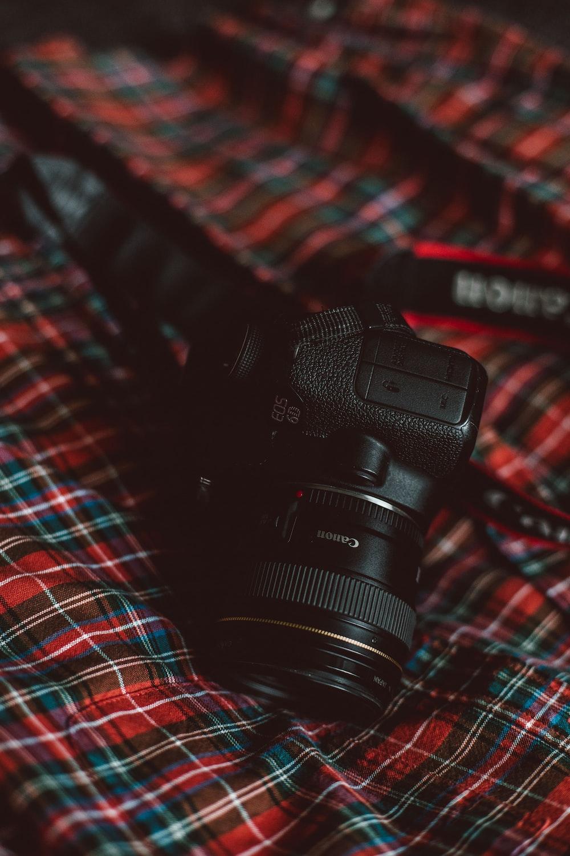 black Canon camera on plaid textile