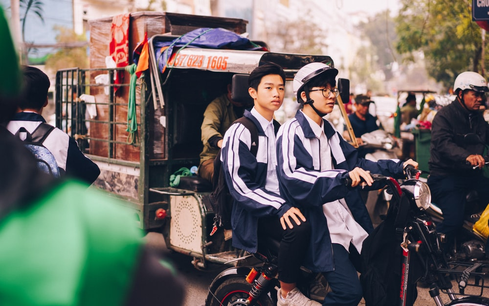 two men riding motorcycle beside auto rickshaw