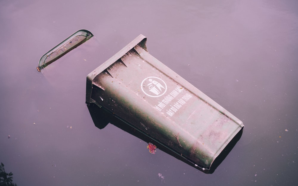 gray garbage bin on body of water