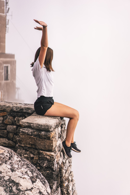 woman sitting on edge while raising hand