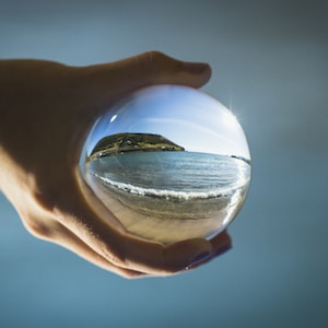 person holding glass ball reflecting sea during daytime