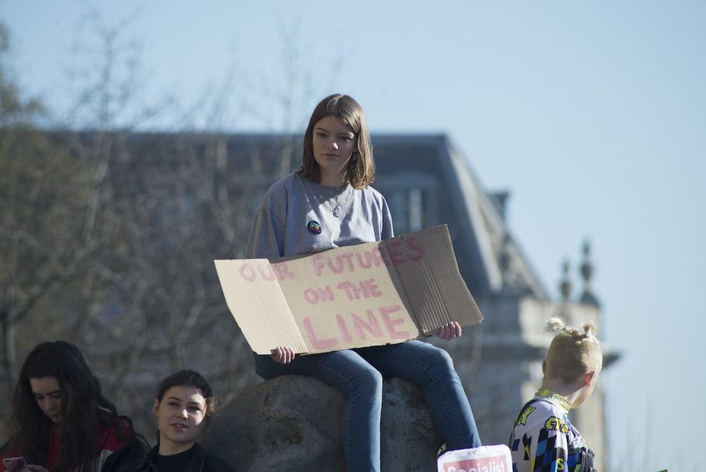 woman holding cardboard signage