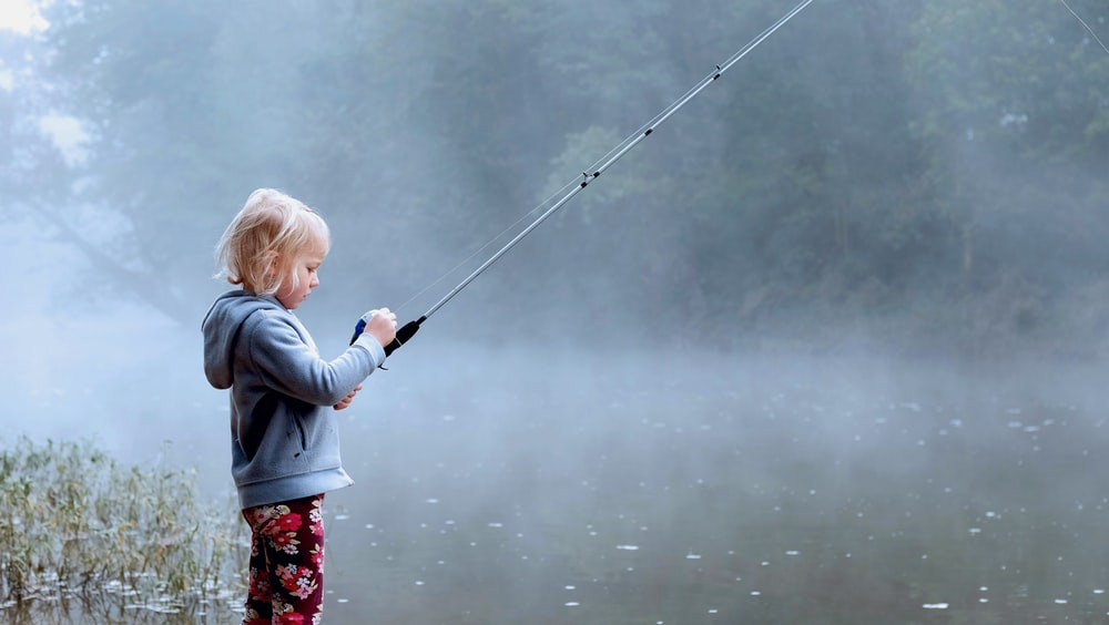toddler wearing gray hoodie holding fishing rod