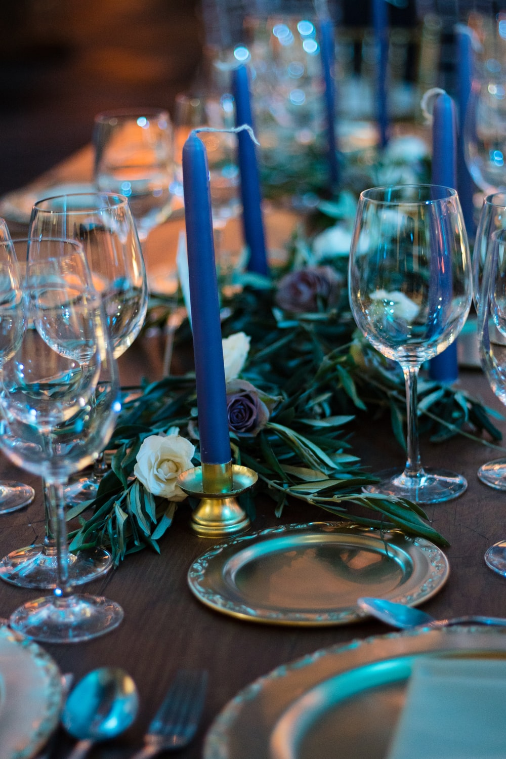 clear wine glasses and blue taper candles