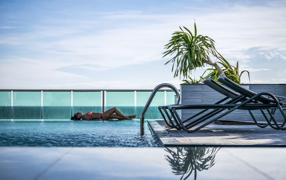 woman lying at pool beside fence during daytime