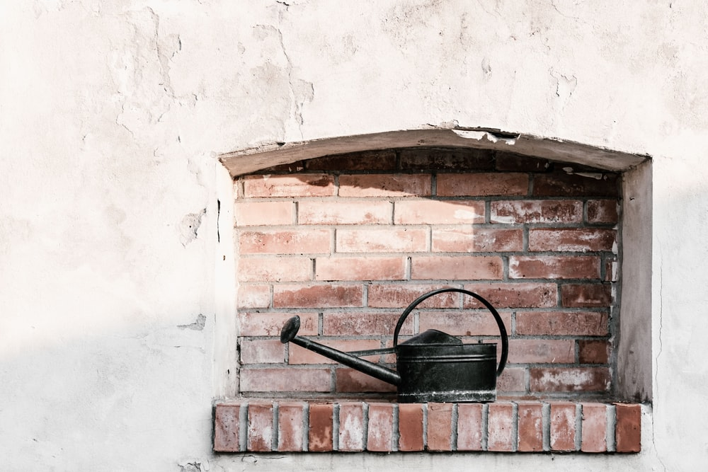 black watering can on brick wall
