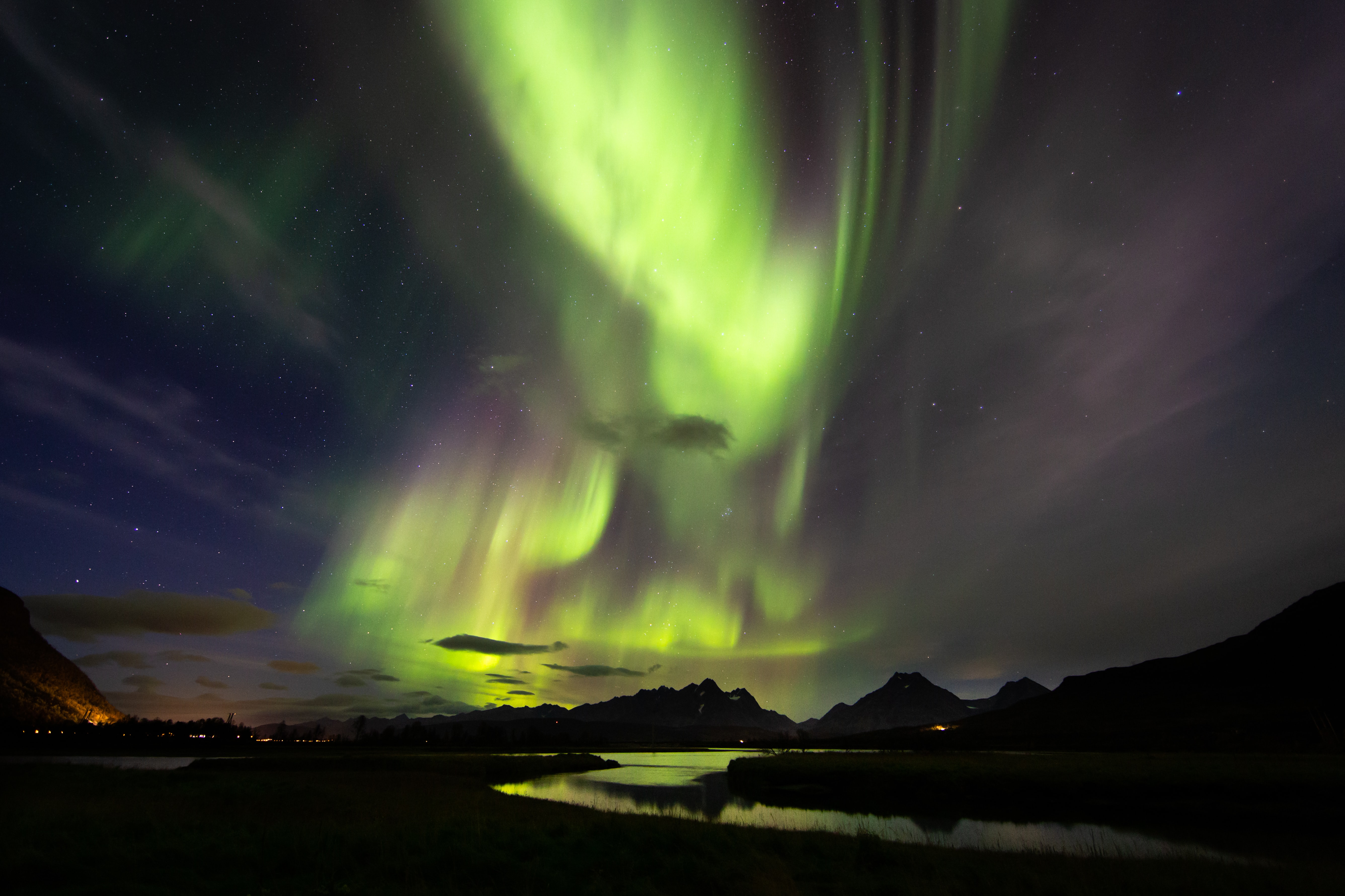 Aurora over body of water and mountain