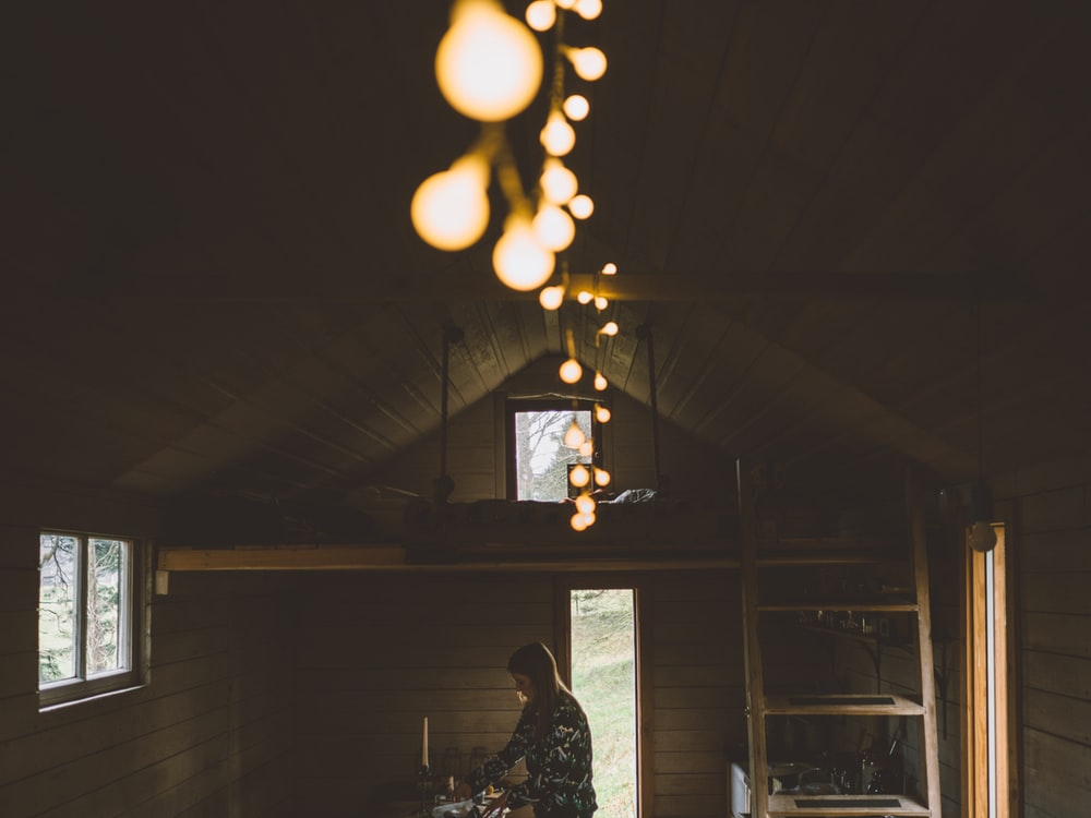 woman standing inside brown wooden house