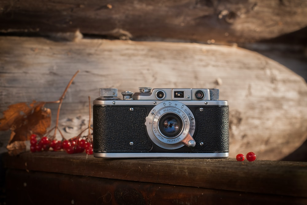 black and gray SLR camera on brown surface