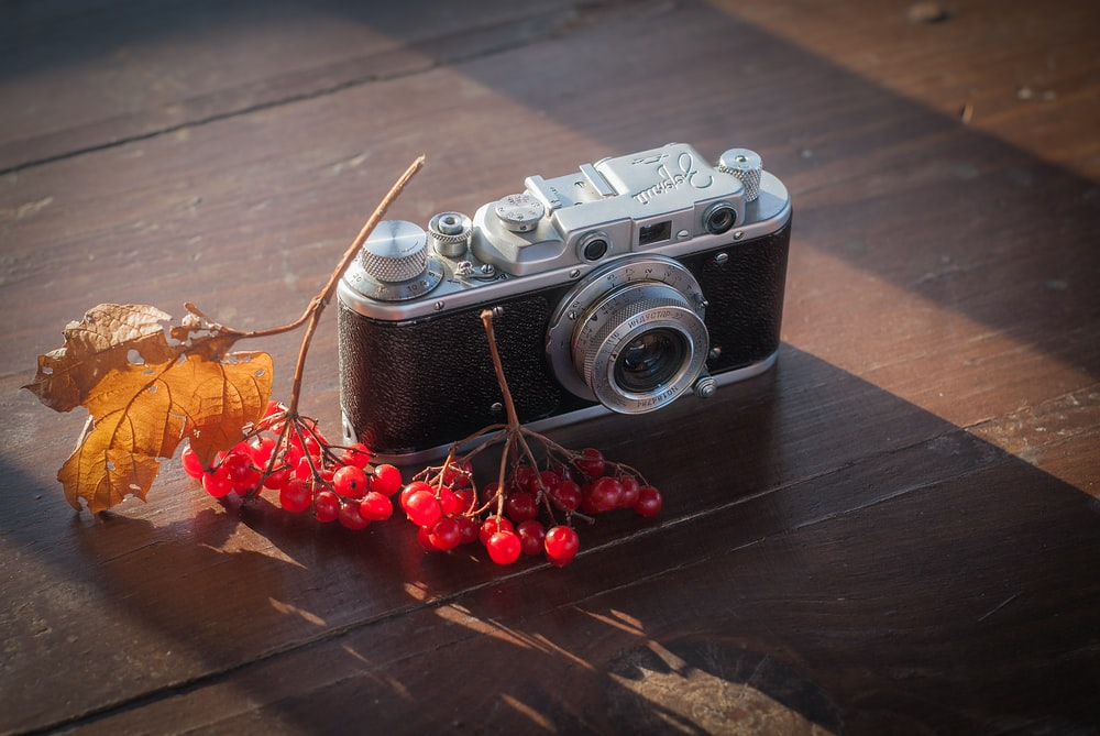 black camera beside cherries