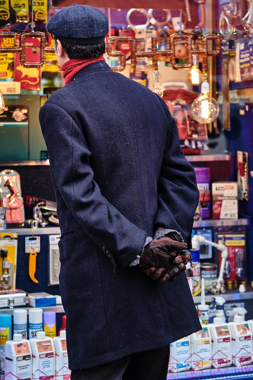 man staring at the store behind glass wal