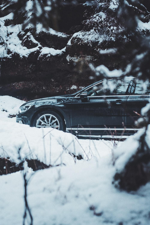 black sedan covered with snow