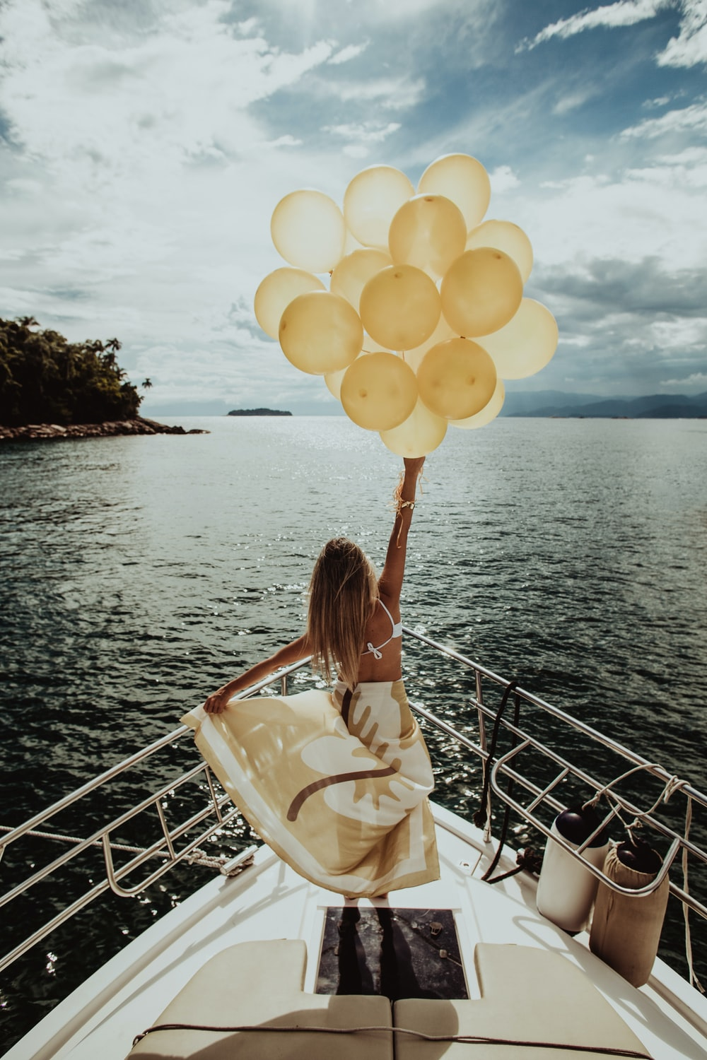woman holding gold balloons while standing on a yacht