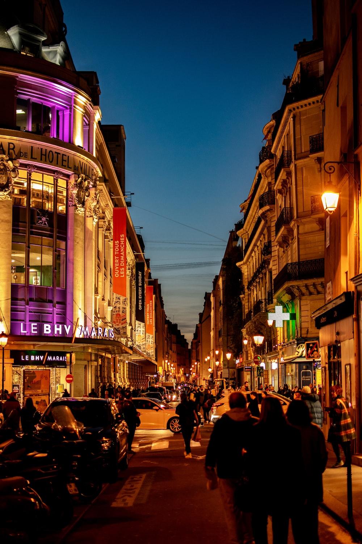 people walking on street beside building during night time