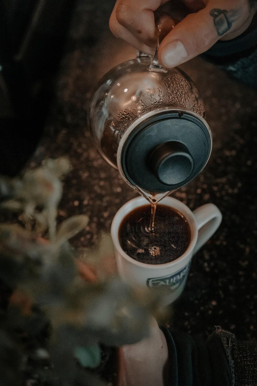 person pouring coffee on mug