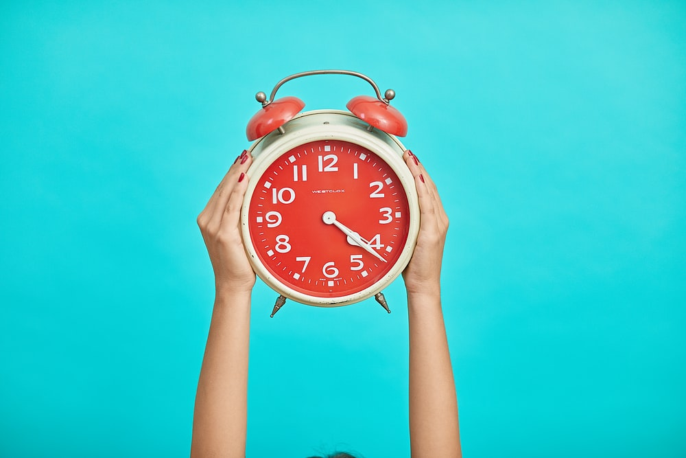 person holding red and beige twin bell analog alarm clock
