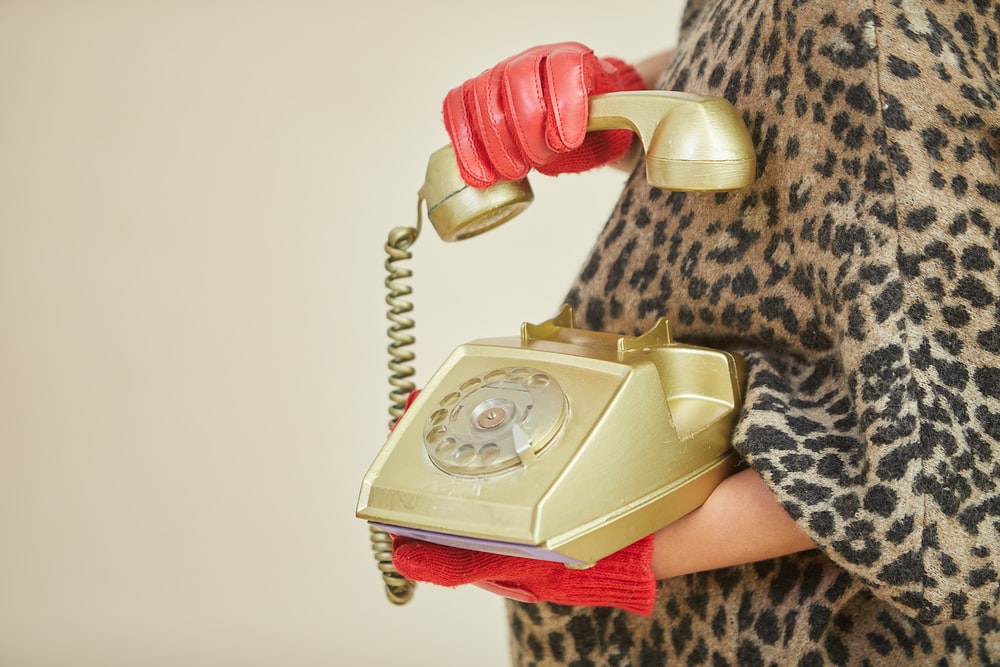 person holding gold-colored rotary telephone