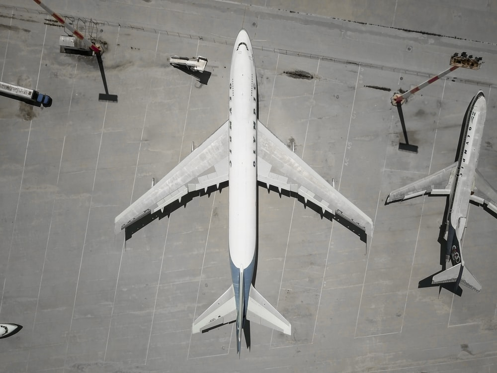 white airplane parked beside another airplane