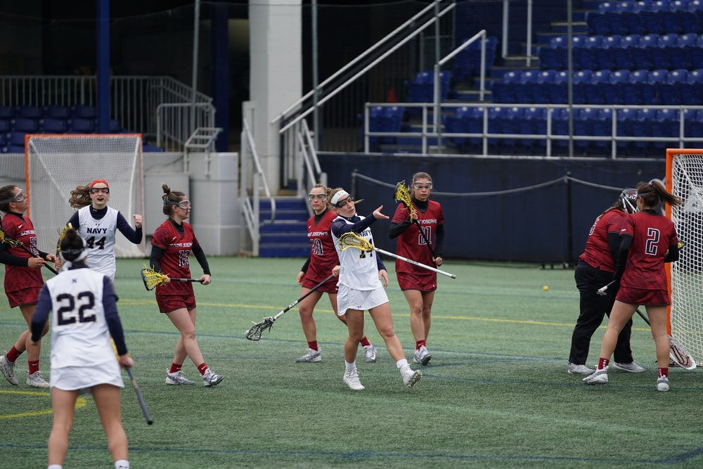 women playing lacrosse on field
