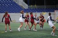 women playing lacrosse on field