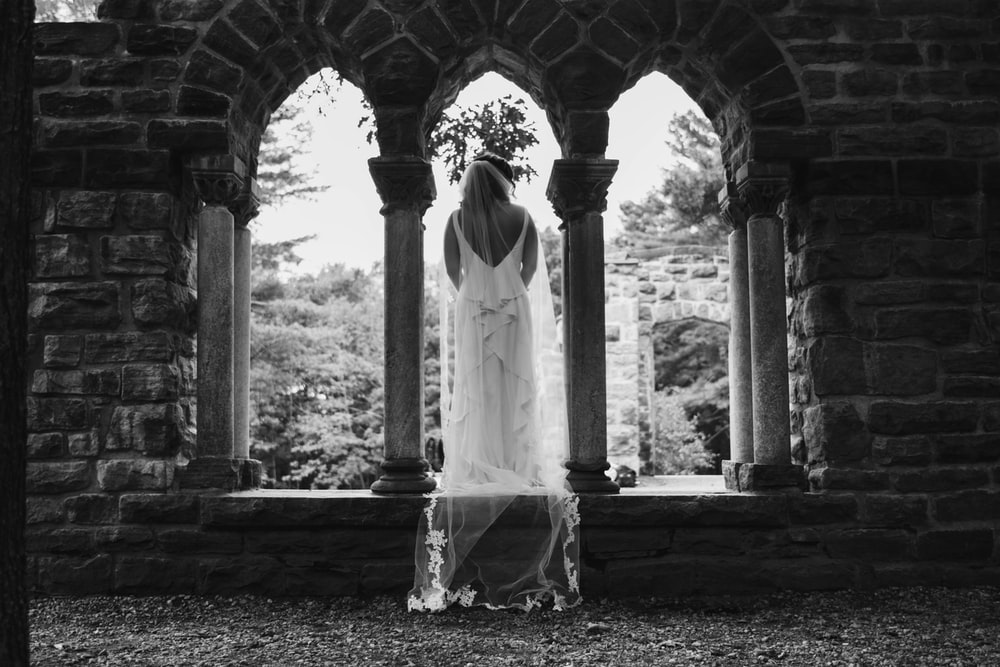 grayscale photography of woman standing between arch and pillar