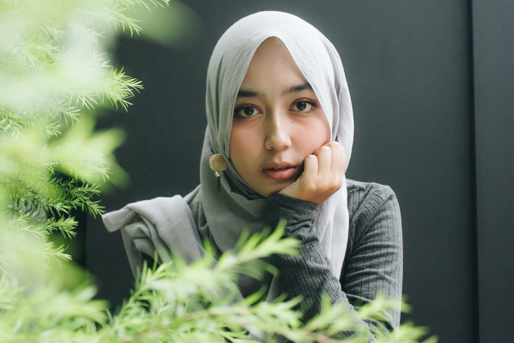 woman wearing gray long-sleeved top and gray hijab right hand on cheek