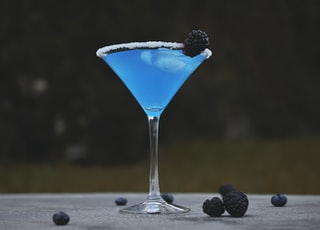 martini glass with mulberry and blue liquid