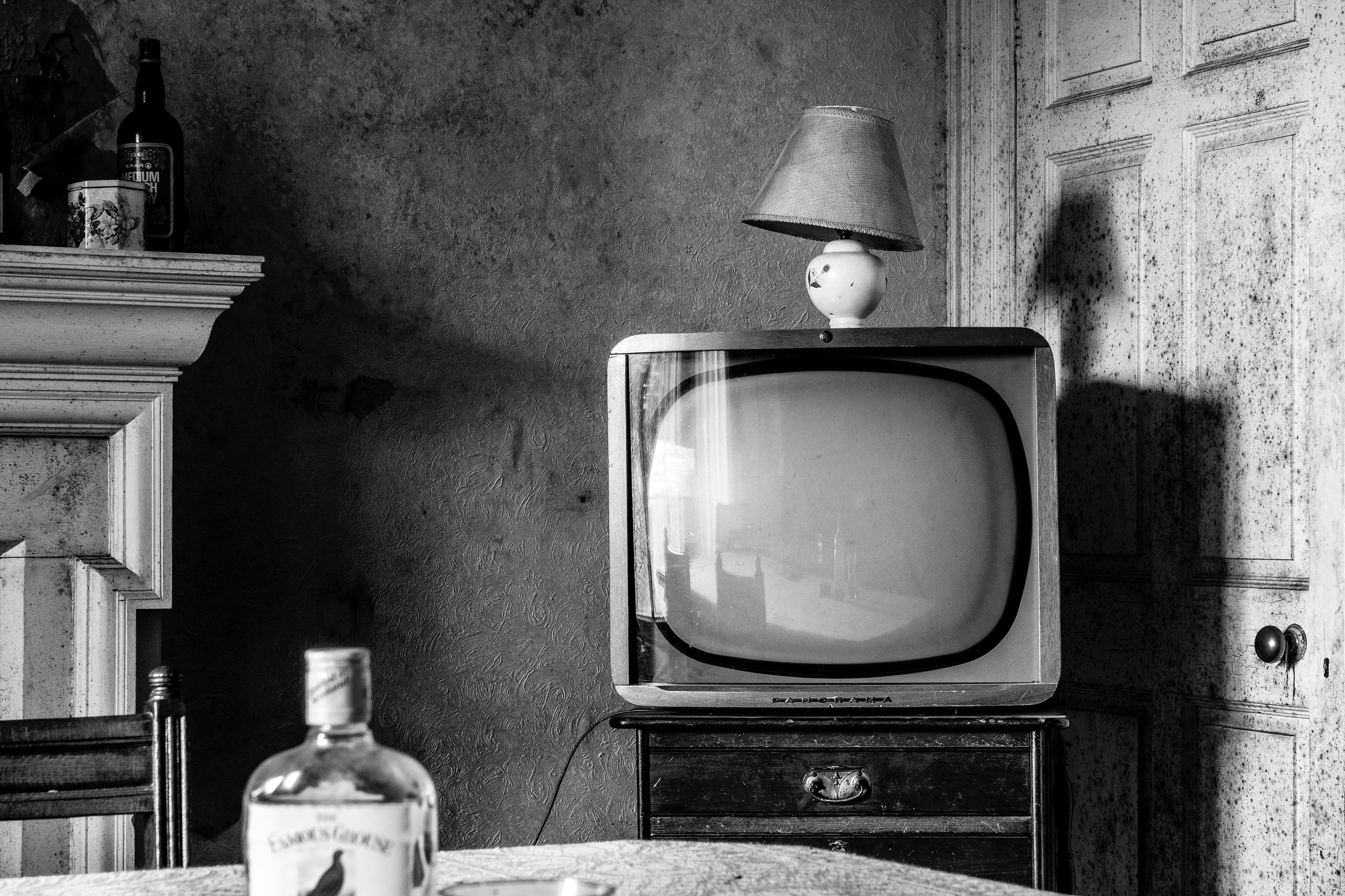 bottle of liquor on table with CRT television across beside the close door