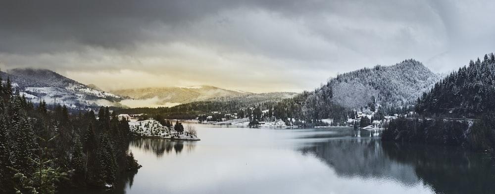 body of water between mountain during daytime