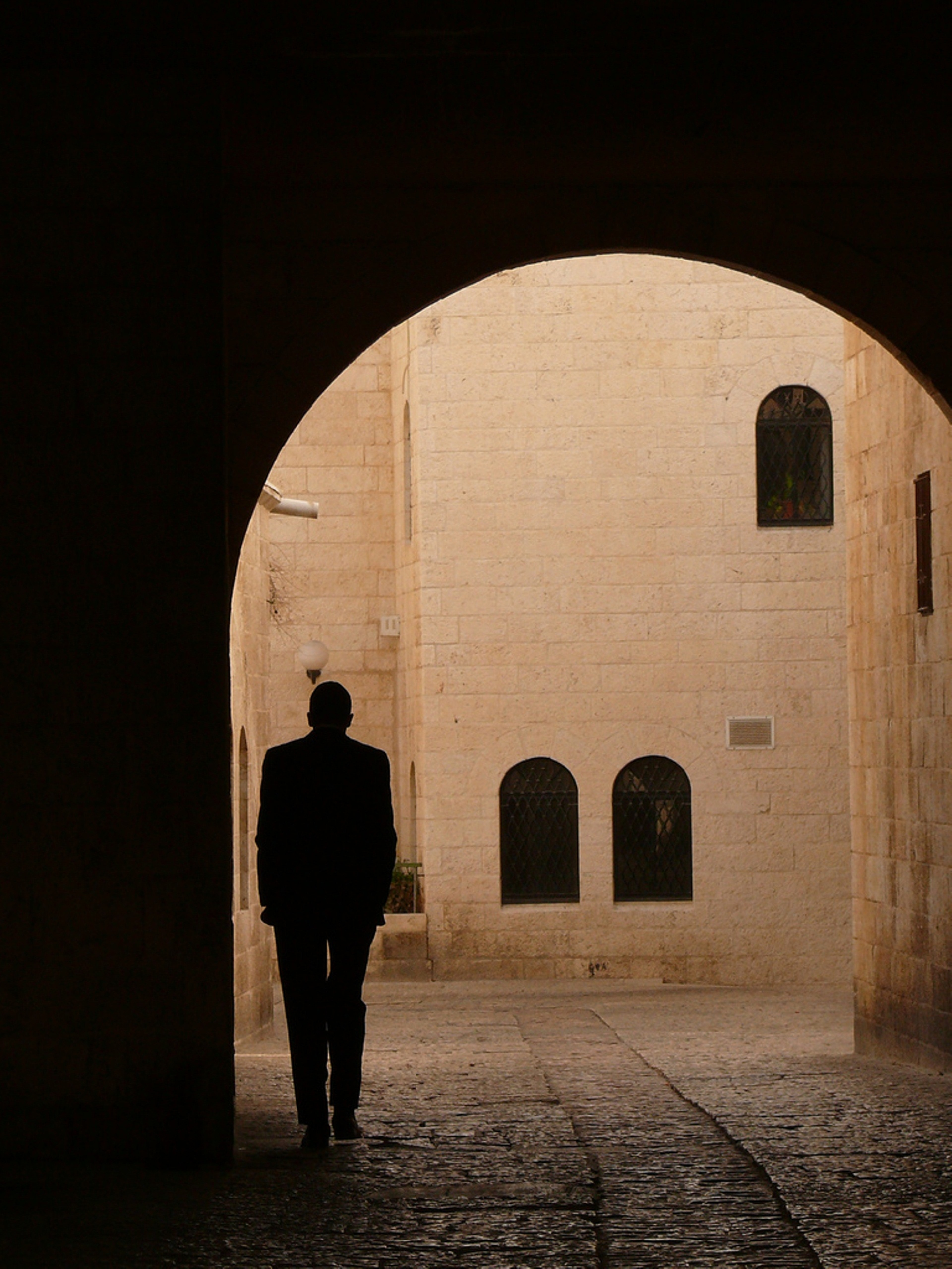 silhouette of person walking on narrow pathway