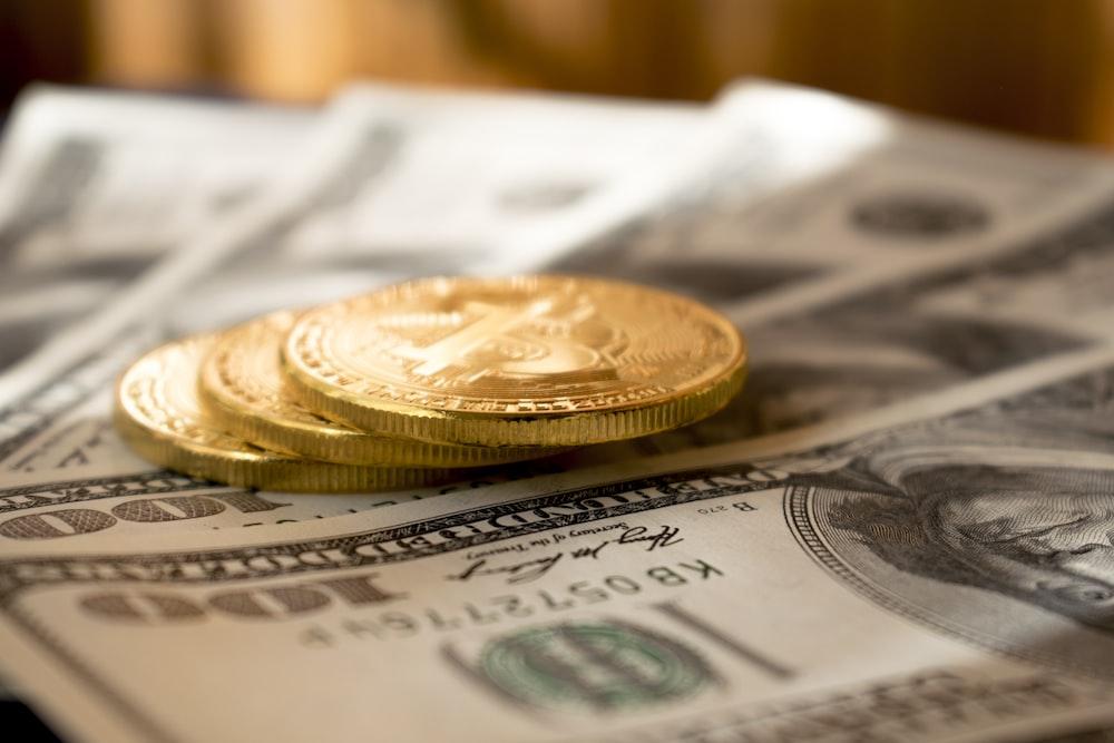 100米ドル紙幣に3つの丸い金色のコイン